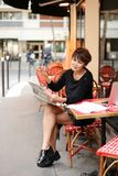 Middle-aged woman discusses new edition of newspaper. Woman sitting at table of street cafe skimmed through new newspaper. Female with short haircut dressed in Royalty Free Stock Photography