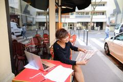 Middle-aged woman discusses new edition of newspaper. Woman sitting at table of street cafe skimmed through new newspaper. Female with short haircut dressed in Stock Photography