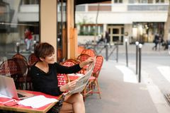Middle-aged woman discusses new edition of newspaper. Woman sitting at table of street cafe skimmed through new newspaper. Female with short haircut dressed in Stock Photo