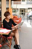 Middle-aged woman discusses new edition of newspaper. Woman sitting at table of street cafe skimmed through new newspaper. Female with short haircut dressed in Stock Image