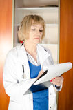 Middle aged woman doctor taking notes. In clipboard Royalty Free Stock Photo