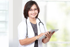 Middle aged woman doctor using tablet computer Royalty Free Stock Photo