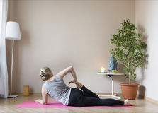 Middle aged woman doing yoga indoors Royalty Free Stock Photography
