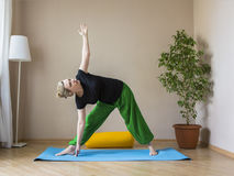 Middle aged woman doing yoga indoors Stock Photos