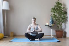 Middle aged woman doing yoga indoors Royalty Free Stock Photos