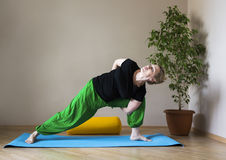 Middle aged woman doing yoga indoors Royalty Free Stock Photo
