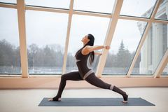 Middle aged woman doing yoga in Virabhadrasana One or Warrior One yoga pose on the mat in front of large windows., exercise fitnes royalty free stock images