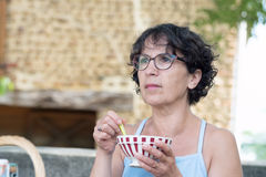 Middle-aged woman drinking a chocolate. Amiddle-aged woman drinking a chocolate in the garden Stock Image