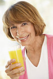 Middle Aged Woman Drinking Fresh Orange Juice Stock Photo