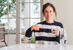 Beautiful middle age woman at home. Middle aged woman drinking a glass of water with surprise face pointing finger to himself Stock Image
