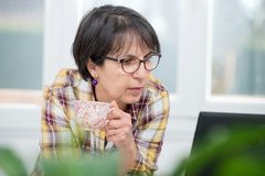 Middle-aged woman drinks a cup of coffee. A middle-aged woman drinks a cup of coffee Stock Images