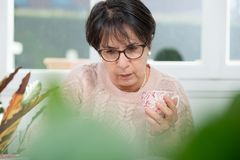 Middle-aged woman drinks a cup of coffee. A middle-aged woman drinks a cup of coffee Stock Photo
