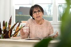 Middle-aged woman drinks a cup of coffee. A middle-aged woman drinks a cup of coffee Stock Image