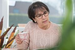 Middle-aged woman drinks a cup of coffee. A middle-aged woman drinks a cup of coffee Royalty Free Stock Image
