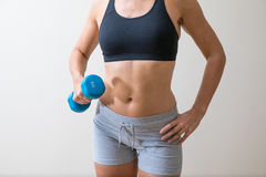Middle aged woman with a dumb bell. Middle aged woman in gym gear with a blue dumb bell Royalty Free Stock Photos