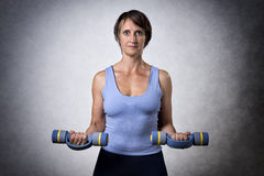 Middle aged woman with dumbbells Royalty Free Stock Photography