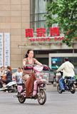 Middle-aged woman on e-bike in city center, Nanjing, China. NANJING-MAY 25-2014. Middle aged woman on e-bike. An estimated 200 million Chinese now use e-bikes, 1 royalty free stock photos