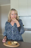 Middle-aged Woman Eating Cheese and Biscuit. Royalty Free Stock Image