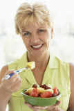 Middle Aged Woman Eating Fresh Fruit Salad.  Royalty Free Stock Photography