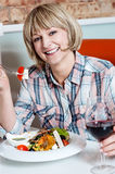 Middle aged woman eating healthy food. Pretty woman enjoying her meal in a restaurant Stock Image