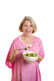 Middle aged woman eating salat. Blond woman in her 50s eating salat out of a bowl, copy space, isolated Stock Images