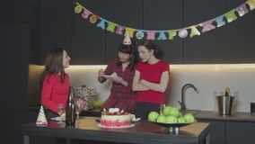 Female eating cake at her birthday party alone. Middle aged woman enjoing taste of festive treat while adult daughters coming into kitchen to celebrate mother`s stock footage