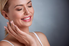 Middle aged woman enjoying in face cream Stock Image