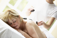 Middle Aged Woman Enjoying Hot Stone Treatment royalty free stock photo