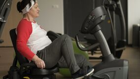 Middle aged woman with excess weight working out on stationary bike