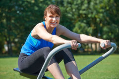 Middle Aged Woman Exercicing On Rowing Machine In Park Stock Images