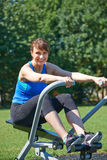Middle Aged Woman Exercising On Rowing Machine In Park Royalty Free Stock Image