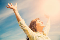 Middle aged woman feeling free. Attractive middle aged woman enjoying the sun and nature with outstretched arms. Freedom concept Stock Image