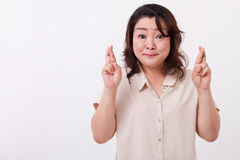 Middle aged woman with finger crossed Royalty Free Stock Image