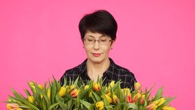 A middle-aged woman with flowers. The concept of floristry. A middle-aged woman with tulips flowers. The concept of floristry stock video footage