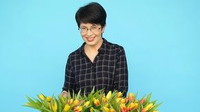 A middle-aged woman with flowers. The concept of floristry. A middle-aged woman with tulips flowers. The concept of floristry stock video