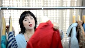 Middle-aged woman is fond of second-hand shopping boutique. Mature adult woman is snapping selfies with a red blouse in a second-hand shop. She enjoys shopping stock video footage
