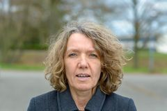 Middle aged woman front portrait with open mouth. Middle aged woman in grey coat, with wrinkled face, curly hair and pale blue eyes front portrait with open royalty free stock image