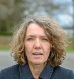 Middle aged woman front portrait with open mouth. Middle aged woman in grey coat, with wrinkled face, curly hair and pale blue eyes front portrait with open stock photos