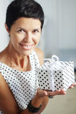 Middle aged woman with a gift Royalty Free Stock Images