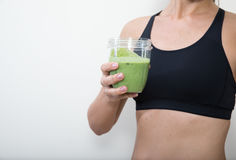 Middle aged woman with a green smoothie. Stock Photos
