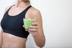 Middle aged woman with a green smoothie. Middle aged woman with a glass of green kale smoothie Stock Photography