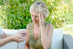A middle-aged woman has a headache. Outside Royalty Free Stock Image