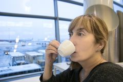 Woman drinking coffee in airport royalty free stock images