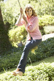 Middle Aged Woman Having Fun On Rope Swing Royalty Free Stock Photos