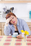 Middle aged woman with headache in kitchen Stock Photo