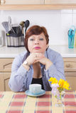 Middle aged woman with headache in kitchen Royalty Free Stock Photo