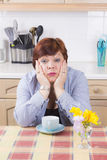 Middle aged woman with headache in kitchen Stock Photos