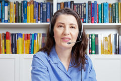 Middle aged woman headset office. Experienced woman with headset and a blue shirt in a library, talking with someone via the internet, as seen through the webcam Royalty Free Stock Photo