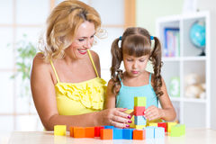 Middle aged woman helping her daughter build Stock Photo