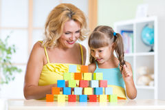 Middle aged woman helping her preschooler daughter Stock Image